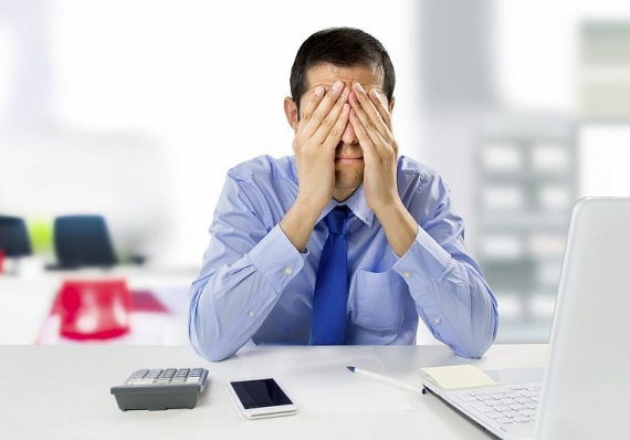 Man behind a computer covering his face in frustration